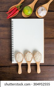 Recipe notebook, rice, Red chilli, garlic and lemon on wood texture background