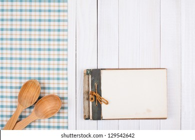 Recipe notebook, tablecloth on white wood background