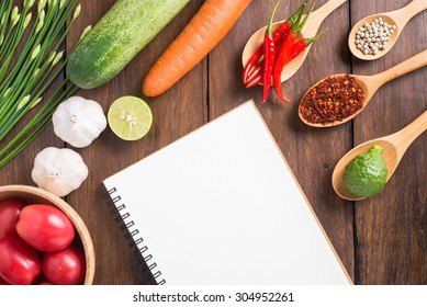 Recipe notebook, tomatoes, Red chilli, garlic and lemon on wood texture background