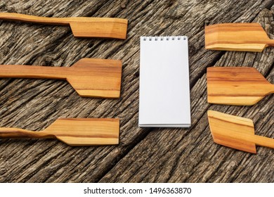 Recipe notepad with kitchen tools on old wooden background.