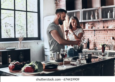 Recipe requires a lot of loving. Beautiful young couple preparing a healthy meal together while spending free time at home
