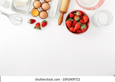 Recipe for strawberry pie. Raw ingredients for cooking strawberry pie or cake on white background with copy space (eggs, flour, milk, sugar, strawberry), top view, flat lay. Bakery background