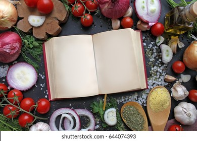 Recipe template with recipe book, spice, onion, garlic, tomatoes and greens on black background. Mock up, copy space, top view.