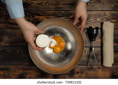 """The recipe for tiramisu preparation, part second """"beating of yolks of egg"""". Products on a wooden table: egg yolk, nimbus, icing sugar. Mixing of yolks of egg and icing sugar."""