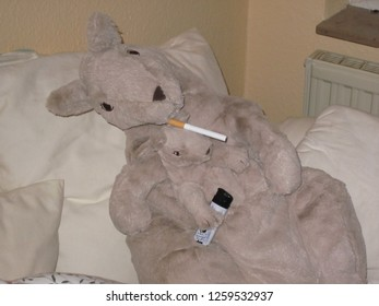 A reckless stuffed mother kangaroo is smoking a cigarette with her offspring in the pouch. They are sitting casually on the living room couch and the health risk of passive smoking is neglected.