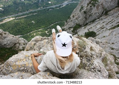 Reckless young woman sitting on high steep cliff. Back view.