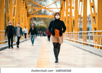 A reckless young Woman walk on crowded street with a mask in a quarantine period because of pandemic global danger.