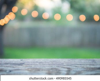 Reclaimed wood board with defocused decorative string lights in the background with green grass
