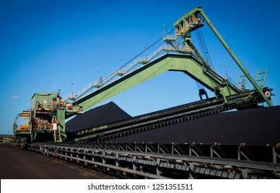 Reclaimer Stacker in a coal mine for bulk material handling. Coal mountain maker. Fossil fuel industry, Environmental challenge, Climate Change.