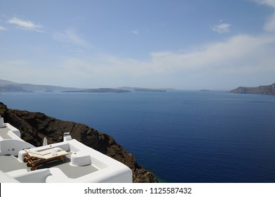 Recliner Chairs for love couples toward Famous stunning view of aegean sea above the volcanic caldera in the village of Oia in Santorini island, Greece