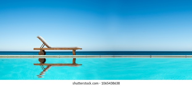 Reclining chair near a swimming pool, sea and blue sky panoramic background
