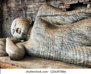 A reclining figure of Buddha is carved into the stone cliffs at the historic landmark of Gal Vihare in the ancient city of Polonnaruwa in Sri Lanka.