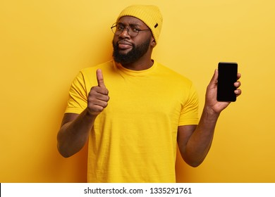 I recommend buying this gadget! Satisfied black unshaven man hods modern cell phone, shows thumb up, really likes device, looks assertive, wears yellow hat and t shirt in one tone with background