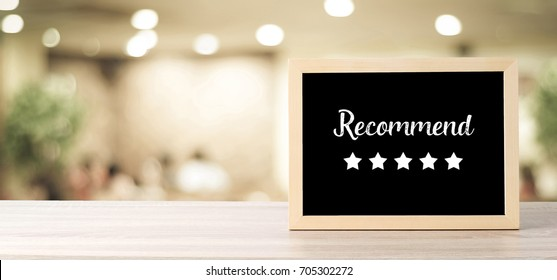 Recommend and five star on blackboard standing over blur restaurant background, copy space for text, food and drinks background, banner