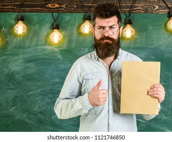 Recommendation concept. Bearded hipster holds book, chalkboard on background. Teacher in eyeglasses recommends book, thumbs up. Man with beard and mustache on serious face stand in front of chalkboard