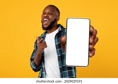 Recommendation. Portrait of excited black guy holding big smartphone with white blank screen in hand, showing close to camera and pointing at device. Gadget with empty free space for mock up, banner - Shutterstock ID 2029029191