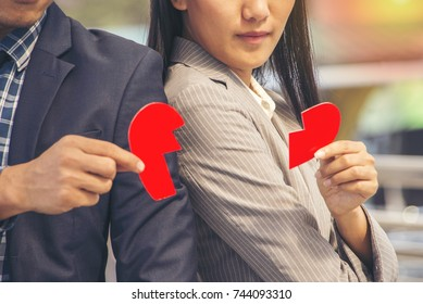 Reconciliation concept. Couple reconciles  hand holding a red paper broken heart  for divorce or reconcile  or reconcile connecting a broken heart.