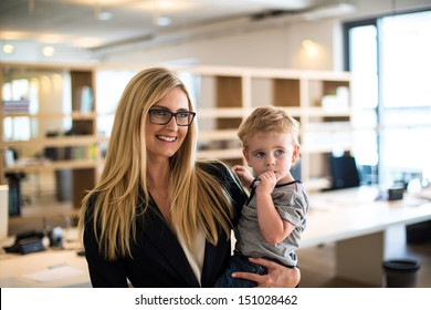 Reconciliation of family and work life: Attractive blond woman in business attire proudly carrying a small boy in her arm in office environment