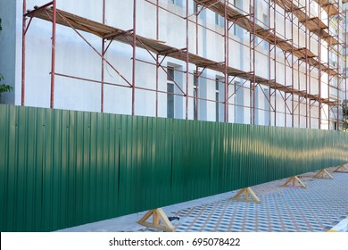 Reconstruction building with external insulation and plaster and with using of scaffolding. Temporary metal fence around the construction site