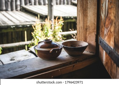 Reconstruction of a ceramic medieval mug and a small bowl on the windowsill of a wooden ancient house. Medieval crafts. Green meadow background. Wooden window frame. Vintage home decoration idea.