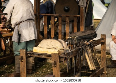 Reconstruction of the forge. Old crafts. Craftsmen rest from work. Blacksmith Furs. Metal tools. Blacksmith forge. Medieval historical role-playing games. Dressed in an old outfit. Bugle.