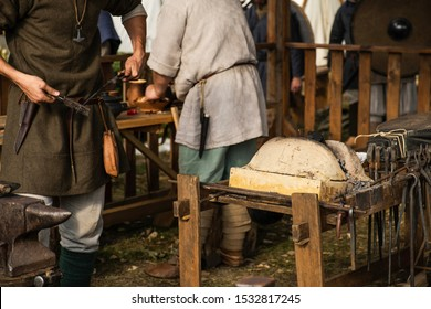 Reconstruction of old crafts. A craftsman in historical clothing bends an iron rod with metal tongs. A blacksmith forges a metal product. Dressed in an old outfit. Ancient metallurgy.
