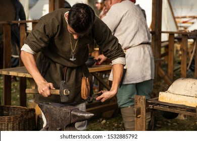 Reconstruction of old crafts. A craftsman in historical clothing is hammering on the anvil. A blacksmith forges a metal product. Dressed in an old outfit.