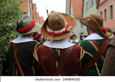 Reconstructors in musketeers clothes on a city holiday