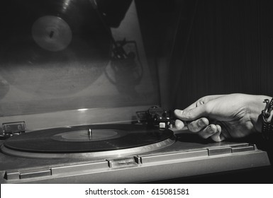 Record player with a hand starting the music