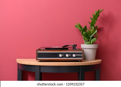 Record player with vinyl disc on table near color wall