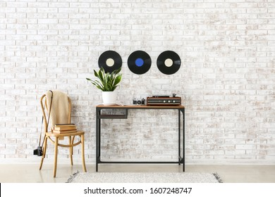 Record player with vinyl disc on table in interior of room