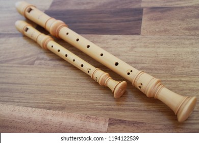 recorder, wooden flute on a wood table.
