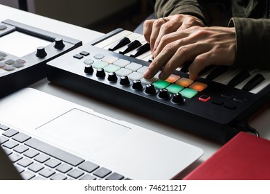 Recording electronic music track with portable midi keyboard on laptop computer in home studio. Producing and mixing music, beat making and arranging audio content with professional audio devices