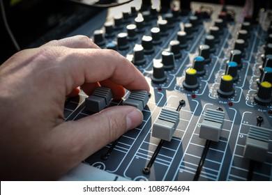 Recording engineer's hand adjusts volume/fader knob on audio sound board.