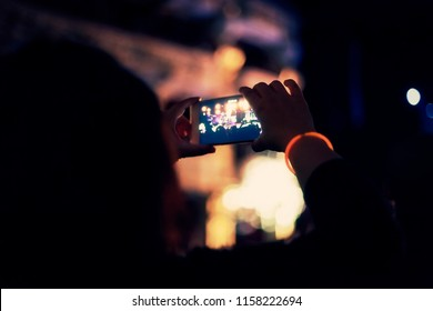 Recording a pop show concert with a smartphone, a bright colorful music show seen through another screen.