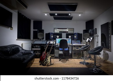 Recording studio control room complete with mixing desk, computer and outboard equipment. Also in the image are guitars, keyboard, microphone and synthesisers.