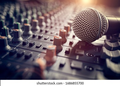 Recording studio mixing desk with microphone on mixer control desk