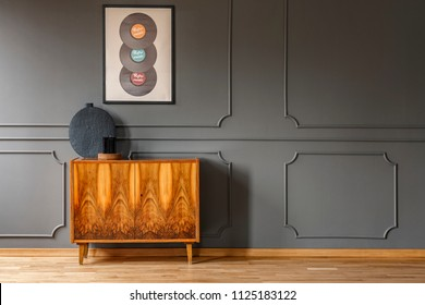 Records on grey wall with molding above wooden cabinet in vintage living room interior. Real photo. Place your lamp here