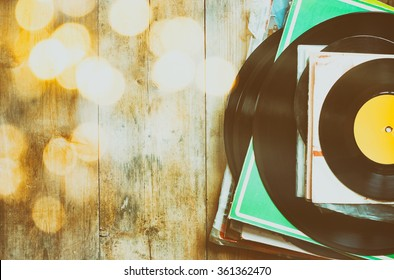 records stack over wooden table and vintage light leaks. filtered image
