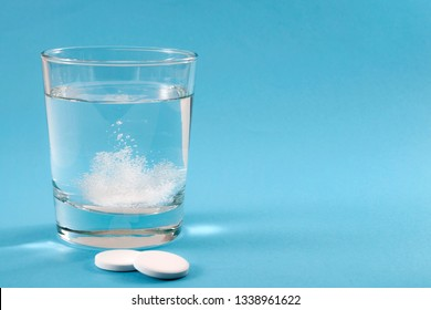 Recovering from a hangover and nursing a headache with aspirin concept with effervescent drink tablet dissolving in water with two tablets outside the glass isolated on blue background with copy space