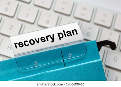 recovery plan is on a label of a blue hanging file. In the background a computer keyboard