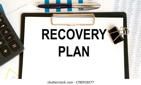 Recovery Plan word written on paper. On the background of accounting, charts and glasses.