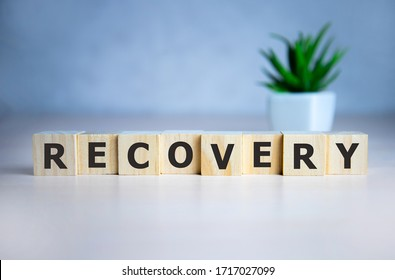 RECOVERY word concept written on wooden cubes lying on a light table and light background.
