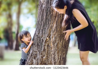 Recreation & Activities of Asian family holidays, Mommy did playing hide and seek with her daughter on forest park. Happy a little child sneaking between rough texture the big tree with mom.
