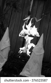 Recreation (fake) Ku Klux Klan members watches a burning cross outside and dusk.  Black and white, photo reportage look and feel, with added film grain. - Shutterstock ID 376523587
