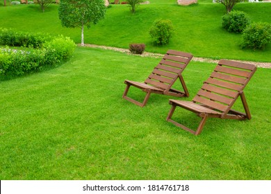 Recreation and tourism advertising. Two Empty brown wooden deck chair or chaise longue, on the green grass of a fresh lawn. Place for text