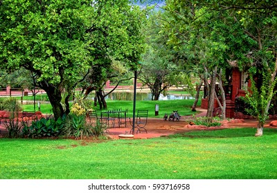 Recreational area with a beautiful garden, a green lawn, a man-made lake in the background. Awesome lodge in Africa. Wonderful landscape. Everything for your relax in a guesthouse.
