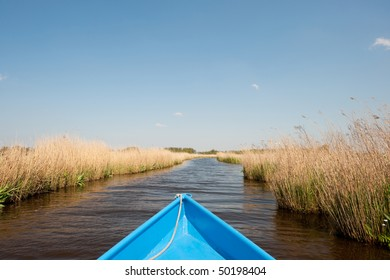 Recreational blue boat in water landscape in Dutch polder