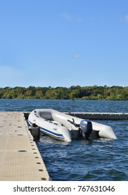 Recreational inflatable white rubber raft with outboard motor tied to wooden dock.. Horizontal marine scene.