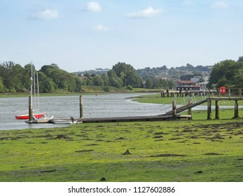 Recreational sailing boats moored by a jetty on the River Medina, Isle of Wight, UK.